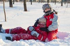 Två pojkar som spelar på vintern, parkerar royaltyfri bild
