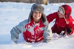 Två pojkar som spelar på vintern, parkerar, utomhus arkivbilder