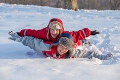 Två pojkar som spelar på vintern, parkerar, utomhus royaltyfri foto