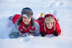 Två pojkar som spelar på vintern, parkerar, utomhus royaltyfri fotografi