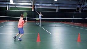 Två pojkar som spelar tennis med äldre flicka eller instruktör Sportövning i rätten arkivfilmer