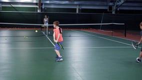 Två pojkar som spelar tennis och har kurs med instruktören på domstolen arkivfilmer