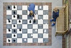 Två pojkar som spelar utomhus- schack Arkivbild