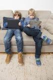 Två pojkar som spelar videospel på en minnestavladator Fotografering för Bildbyråer