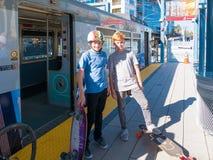 Två pojkar som står på plattformen för tunnelbanaljusstång med skateboarder Arkivbild