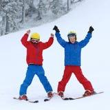 Två pojkar som tycker om vinter, skidar semestern Arkivbild