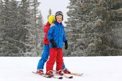 Två pojkar som tycker om vinter, skidar semestern Royaltyfri Foto