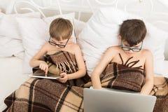 Två pojkar spelar på bärbara datorn och minnestavlan med hunden i säng royaltyfri bild