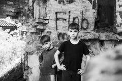 Två pojkar står i en förstörd och övergiven byggnad, svartvitt foto Arrangerat foto arkivbilder
