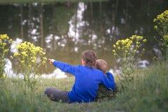 Två pojkar står vid vattnet arkivbilder