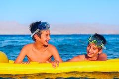 Två pojkar tycker om deras tid på stranden Arkivbilder