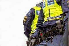 Två poliser, slut upp av övrekroppen med västen och equipm Royaltyfri Fotografi