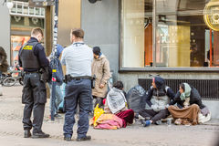Två poliser som ser paipersna av några invandrare arkivfoton