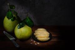 Två pomelos, en platta av pomelokött och en kniv på träten Royaltyfria Foton