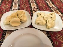 Två portioner av att uppföda den smakliga khinkalien, manti på keramiska vita plattor på tabellen i den nationella georgiska rest arkivbilder
