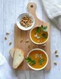 Två portioner av soppa, två skivor av bröd på en skärbräda Royaltyfria Bilder