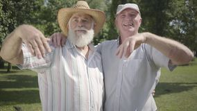 Två positiva gamala män som ser invitera bort den tredje vännen att sammanfoga dem i, parkerar Fritid utomhus Moget folk arkivfilmer
