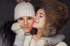 Två positiva kvinnor som bär varma julhattar Royaltyfri Fotografi