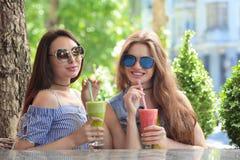 Två positiva unga kvinnor som tycker om den nya smoothien royaltyfria foton