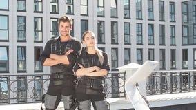 Två positiva ungdomarsom bär ems-konditionvästen och poserar till kameran på gatan arkivfilmer