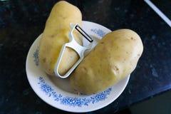 Två potatisar och en skalare på den dekorativa plattan arkivfoton