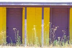Två purpurfärgade dörrar framtill av en gul byggnad arkivbilder