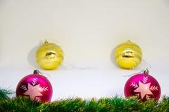 Två purpurfärgade julbollar och två guld- bollar bak dem och julaccessorieson en vit bakgrund Royaltyfri Foto