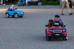 Två pyser rider på röda och blåa elbilar, medan gå med deras föräldrar i en stad, parkerar med gröna träd som skrattar och fotografering för bildbyråer