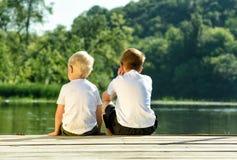 Två pyser sitter på pir på flodbanken Begrepp av kamratskap och broderskap tillbaka sikt fotografering för bildbyråer