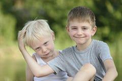Två pyser sitter utomhus Suddiga gröna träd i avståndet Begrepp av kamratskap och broderskap arkivfoton