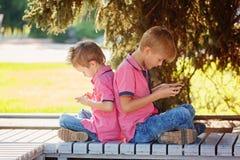 Två pyser som spelar lekar på mobiltelefonen i den soliga dagen, sitt fotografering för bildbyråer