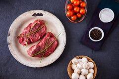 Två rå filetbiffar med champinjoner, körsbärsröda tomater Royaltyfria Bilder