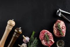 Två rå nya ribeyebiffar med salt, peppar, rosmarin och vitlök på svart bakgrund Fotografering för Bildbyråer