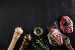 Två rå nya ribeyebiffar med salt, peppar, rosmarin, vitlök och en yxa på svart bakgrund Royaltyfria Bilder