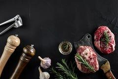 Två rå nya ribeyebiffar med salt, peppar, rosmarin, vitlök och en yxa på svart bakgrund Arkivfoto
