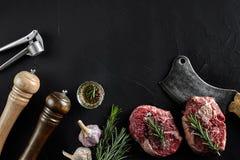 Två rå nya ribeyebiffar med salt, peppar, rosmarin, vitlök och en yxa på svart bakgrund Royaltyfri Foto