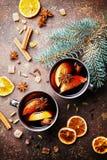 Två rånar av jul funderad vin eller gluhwein med kryddor och apelsinskivor på lantlig bästa sikt för tabell Traditionell drink på arkivfoto