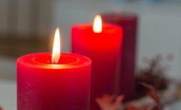 Två röda adventstearinljus begraver ljust på en modern adventkrans arkivfoton