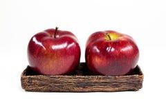 Två röda Apple på lite korg Arkivbild