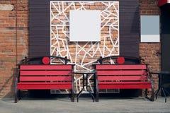 Två röda bänkar som göras av träslats och en tabell arkivbild