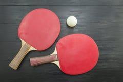 Två röda bordtennisracket på mörk bakgrund Royaltyfri Foto