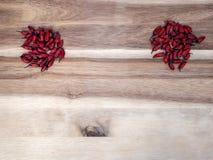 Två röda chilieshögar på ett träbräde royaltyfri bild