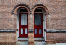 Två röda dörrar i en tegelstenvägg Royaltyfri Fotografi