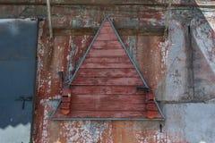 Två röda gamla brandsläckare hänger på en triangulär träställning royaltyfri bild