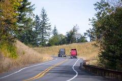 Två röda halva lastbilar och gråa traktorer på den slingriga vägen Royaltyfria Bilder