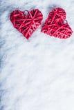 Två röda hjärtor för härlig romantisk tappning tillsammans på en vit snöbakgrund Begrepp för förälskelse- och St-valentindag Royaltyfri Foto