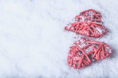 Två röda hjärtor för härlig romantisk tappning tillsammans på en vit snöbakgrund Begrepp för förälskelse- och St-valentindag Royaltyfria Bilder