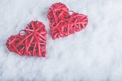 Två röda hjärtor för härlig romantisk tappning tillsammans på en vit snöbakgrund Begrepp för förälskelse- och St-valentindag Fotografering för Bildbyråer