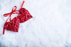 Två röda hjärtor för härlig romantisk tappning tillsammans på vit snövinterbakgrund Begrepp för förälskelse- och St-valentindag Royaltyfri Foto