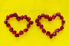 Två röda hjärtor från granatäpplefrö på en platta Arkivfoto
